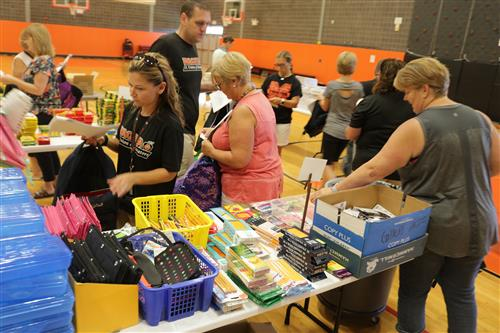 Volunteers stuff backpacks and bags with school supplies in the MMS gymnasium