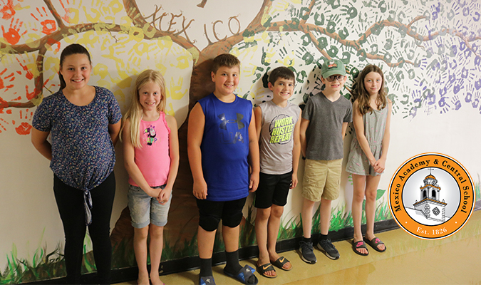 Students entering the fifth grade stand in front of a mural at Mexico MS.