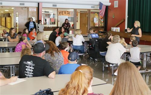 Pictured is a group of students and families listening during orientation.