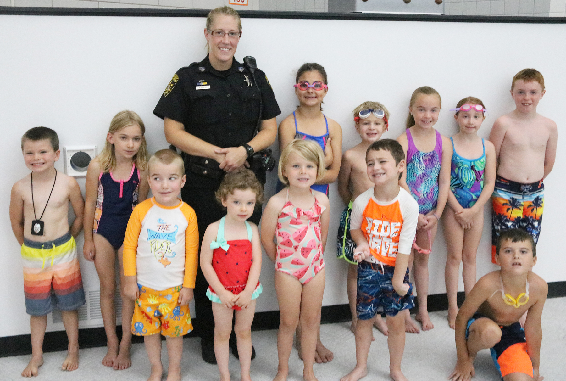 Female sheriff poses by the pool with children that were just swimming