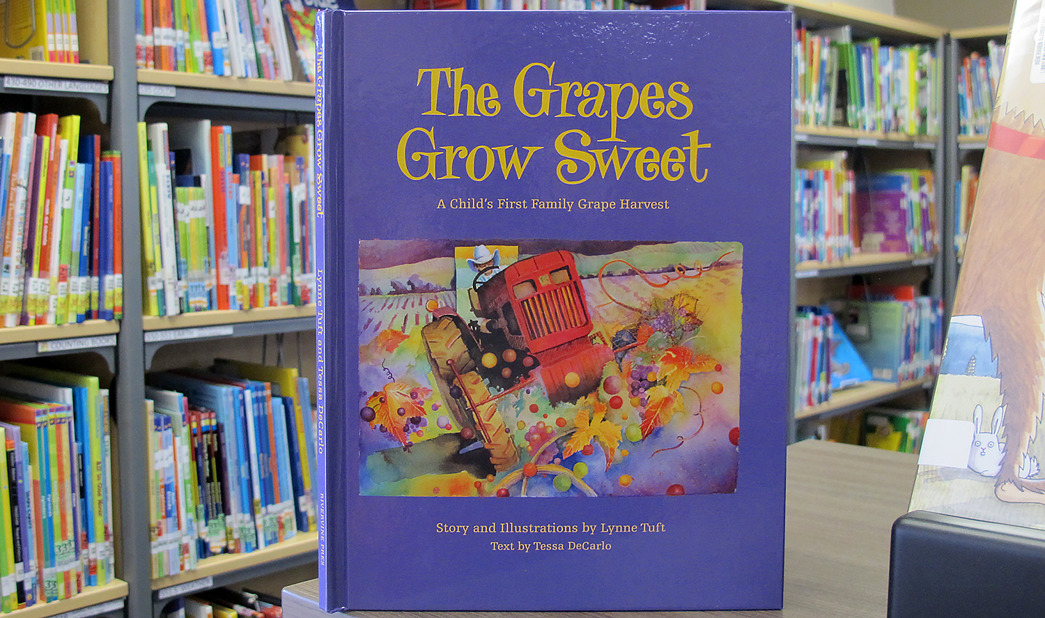 "Purple cover of ""The Grapes Grow Sweet"" by Lynne Tuft and Tessa DeCarlo donated by NY Farm Bureau book"
