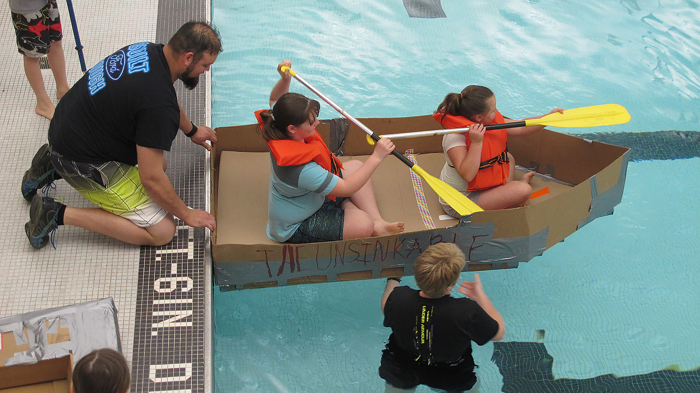 2 students in a cardboard boat get a push from the side of the pool by an adult